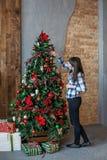La donna allegra orna un albero di Natale a casa Concetto di allegro Fotografia Stock