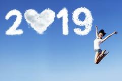 La donna allegra salta con il numero 2019 fotografia stock