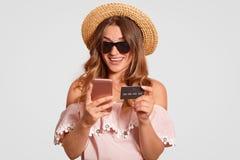 La donna allegra sembrante piacevole attraente fa vestirsi il sorriso a trentadue denti, nel cappello dell'estate, in blusa, in t immagine stock libera da diritti