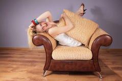 La donna allegra si siede in una poltrona Fotografie Stock Libere da Diritti