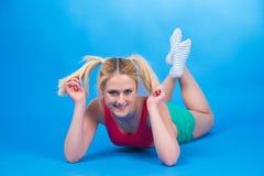 La donna allegra si trova su fondo blu Fotografia Stock Libera da Diritti