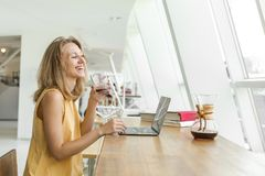 La donna allegra sta bevendo il caffè ed il lavoro immagini stock