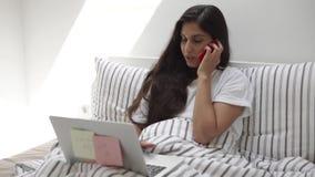 La donna allegra sta lavorando con il taccuino ed il telefono cellulare, trovantesi a letto stock footage