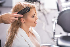 La donna allegra sta sedendosi allo studio del parrucchiere Immagine Stock Libera da Diritti