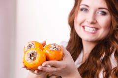 La donna allegra tiene i frutti del cachi del cachi Fotografia Stock Libera da Diritti