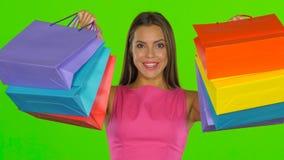La donna allegro guarda fuori da dietro i sacchetti della spesa Schermo verde Fine in su archivi video