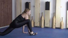 La donna allunga i muscoli della gamba e si siede su cordicella longitudinale in studio archivi video