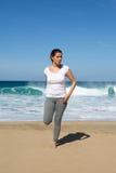 La donna allunga la gamba sulla spiaggia Immagini Stock
