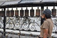 la donna alta chiusa fila la ruota di preghiera al tempio a Kathmandu, Nepal Immagine Stock Libera da Diritti