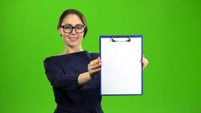 La donna alza una compressa di carta e sorride Schermo verde archivi video