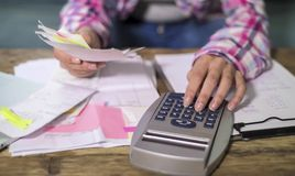 La donna anonima anonima passa il lavoro con le fatture di lavoro di ufficio della banca ed i documenti finanziari che calcolano  fotografia stock