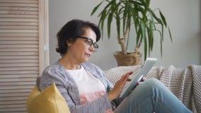 La donna anziana attraente sta praticando il surfing il web facendo uso della compressa sul sofà a casa archivi video