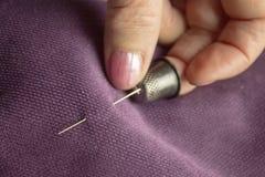 La donna anziana bianca che tiene un ago sul dito medio che indossa un ditale, l'ago perfora fotografie stock
