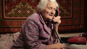 La donna anziana che parla sul telefono con il quadrante rotatorio archivi video