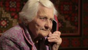La donna anziana che parla sul telefono con la fine del quadrante rotatorio su archivi video