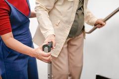 La donna anziana che per mezzo di una canna con la figlia ciao fotografie stock