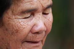 La donna anziana chiude i suoi occhi Fotografie Stock Libere da Diritti
