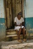 La donna anziana cieca si siede sui punti davanti alla sua casa a Avana Fotografia Stock