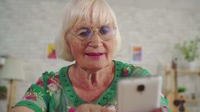 La donna anziana con capelli grigi utilizza uno smartphone che si siede ad una tavola nella fine del salone su archivi video