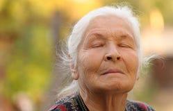 La donna anziana con gli occhi chiusi Fotografia Stock