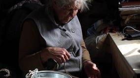La donna anziana con le mani irritate tricotta i nodi su una corda per abbassare un secchio in un pozzo, vita in un villaggio abb