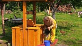 La donna anziana del paesano a bene, l'acqua di tiraggio e lo versano per bucket Immagini Stock