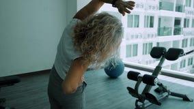 La donna anziana fa gli squattings nella palestra La donna senior della donna anziana fa gli esercizi di uno sport nella palestra archivi video