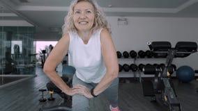 La donna anziana fa gli squattings nella palestra La donna senior della donna anziana fa gli esercizi di uno sport nella palestra stock footage