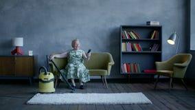 La donna anziana felice ha smesso la pulizia e seduta per rilassarsi e guardare la TV stock footage