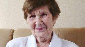 La donna anziana felice, sorridente ride della macchina fotografica stock footage