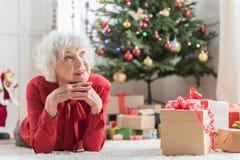 La donna anziana graziosa sta riposando con piacere Fotografie Stock