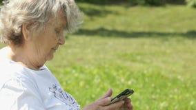 La donna anziana matura tiene uno smartphone all'aperto video d archivio