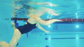 La donna anziana nuota nella piscina - underwater di fucilazione stock footage