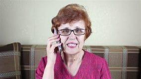 La donna anziana parla dal telefono archivi video