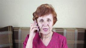 La donna anziana parla dal telefono video d archivio