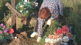 La donna anziana prende la cura delle tombe stock footage
