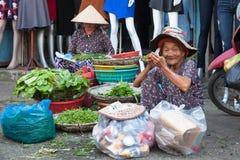 La donna anziana prende una rottura per mangia e riposa alla via del mercato fotografia stock