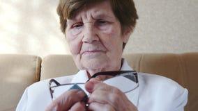 La donna anziana pulisce i suoi vetri archivi video