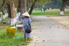 La donna anziana raccoglie la roba da immondizia fotografia stock