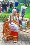 La donna anziana russa torce un filo su una ruota di filatura di legno antica Arte di scomparsa immagini stock