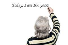 La donna anziana scrive sulla parete con l'indicatore Immagini Stock Libere da Diritti