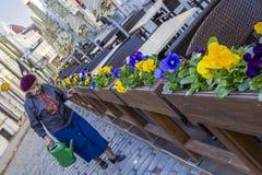 La donna anziana si occupa dei fiori Immagine Stock