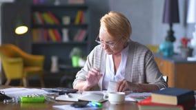 La donna anziana si preoccupa per le fatture considera sul calcolatore ed ottiene turbata video d archivio