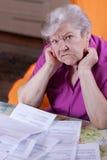La donna anziana si siede davanti ai documenti Fotografia Stock