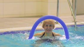 La donna anziana sorridente fa l'esercizio con la tagliatella nella piscina archivi video