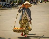 La donna anziana sostiene un onere gravoso delle merci nel carrello della frutta da vendere Fotografia Stock