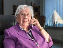 La donna anziana sta dando una chiamata facendo uso di un telefono cellulare fotografia stock