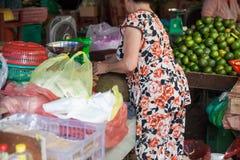La donna anziana sta pelando la giaca al mercato bagnato immagini stock libere da diritti