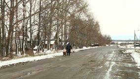La donna anziana va via sulla strada archivi video