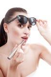 La donna applica un rossetto rosso sulle labbra. fotografie stock